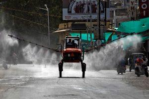 کورونا وائرس کے پھیلاؤکو روکنے کے لیے گجرات کے احمدآباد شہر میں چھڑکاؤ کرتے اہلکار۔ (فوٹو: رائٹرس)