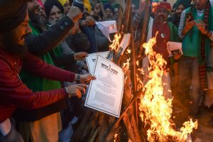 دہلی کے سنگھو بارڈر پر بدھ کوزرعی قوانین کی کاپیاں جلاتے کسان۔ (فوٹو: پی ٹی آئی)
