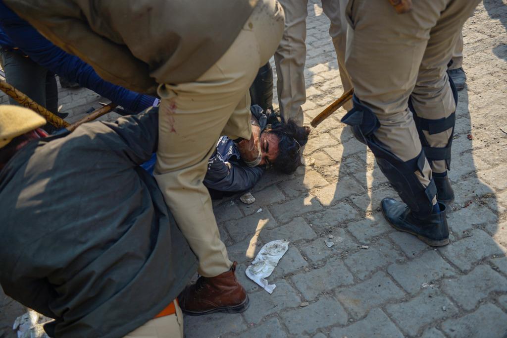 دہلی کے سنگھو بارڈر پر ہوئی جھڑپ کے دوران ایک نوجوان کو پیٹتی پولیس۔ نوجوان پر ایک ایس ایچ او پر حملہ کرنے کا الزام ہے۔ (فوٹو: پی ٹی آئی)