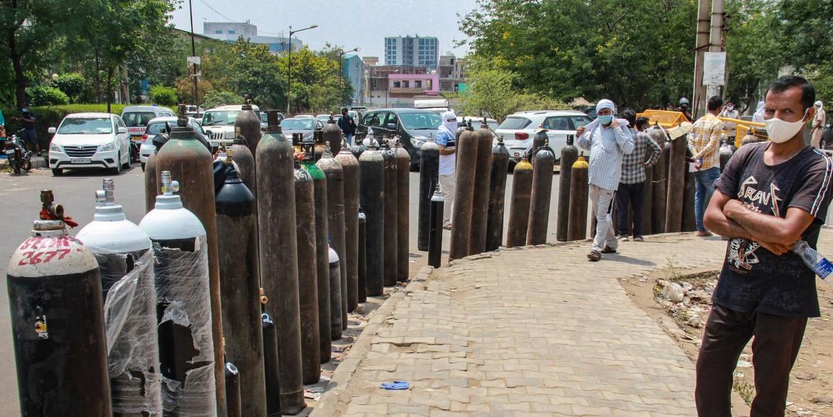 ہریانہ کے مانیسر میں ایک پلانٹ کے باہر آکسیجن سلینڈر بھروانے کی قطار میں کھڑے مریضوں کے اہل خانہ۔ (فوٹو: پی ٹی آئی)